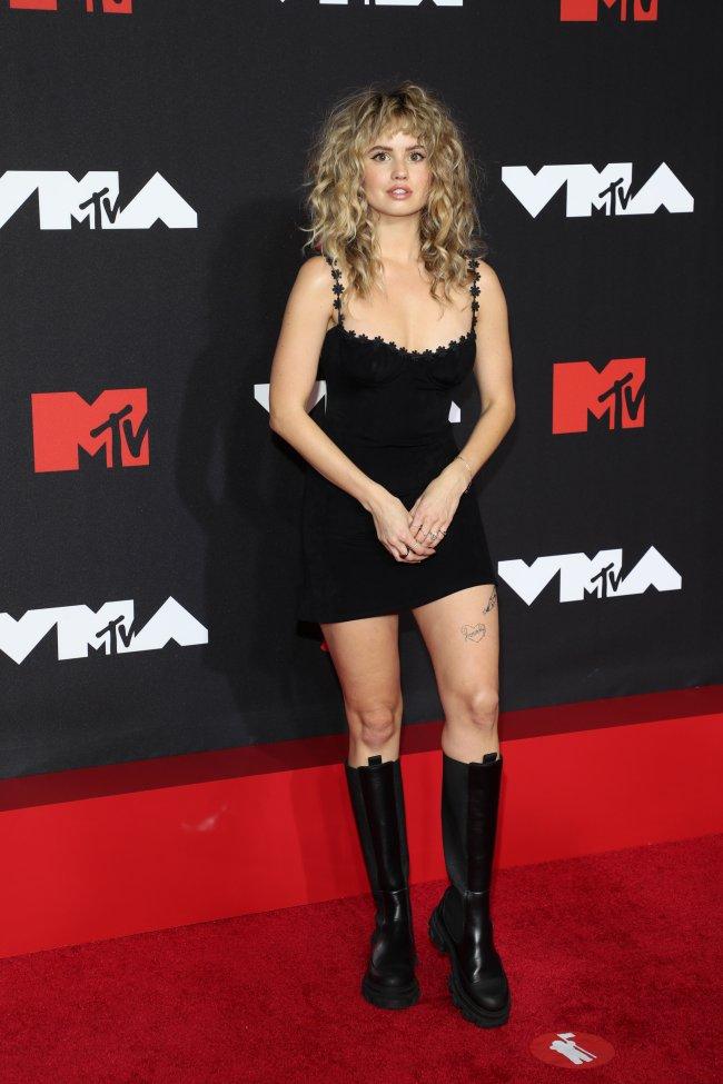 Foto da Debby Ryan no tapete vermelho do MTV Video Music Awards 2021. Ela usa um vestido preto, bota de cano alto preta, cabelo solto e maquiagem básica. Ela olha para a câmera e não sorri.