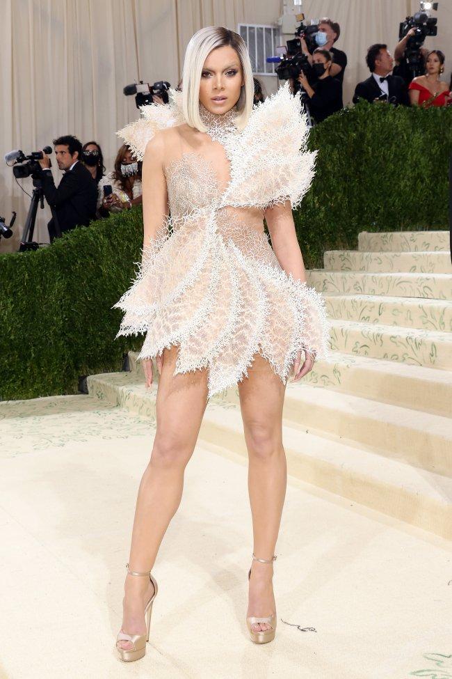 Foto da atriz e cantora Hailee Steinfeld no tapete vermelho do MET Gala 2021. Ela usa um vestido branco e curto, salto alto, cabelo solto loiro e curto e maquiagem clara com a sobrancelha descolorida. Ela olha para a câmera e não sorri.