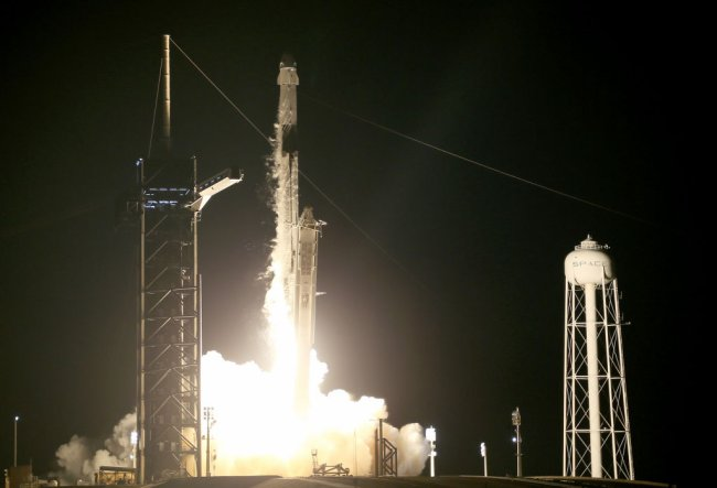 Foguete Falcon, da missão Inspiration4, decolando na Flórida, nos EUA. Está de noite e há muito fogo saindo da parte traseira da espaçonave