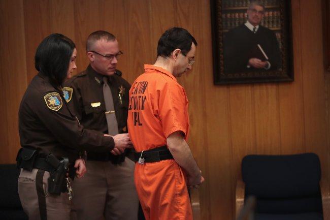 Larry Nassar no tribunal, sendo escoltado por policiais, após ser condenado a até 175 anos de prisão por crimes de assédio sexual
