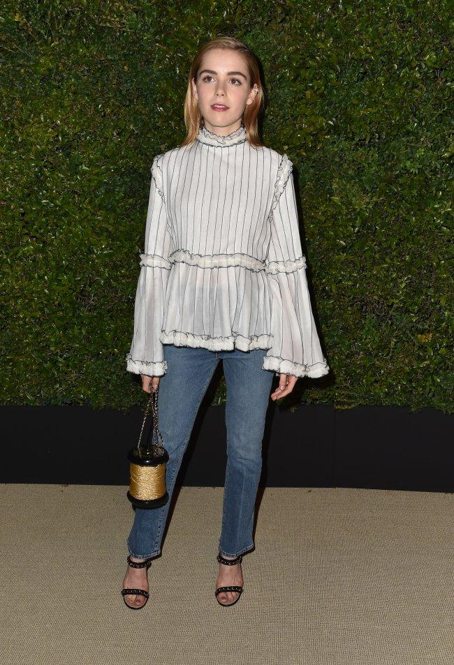 Kiernan Shipka com bolsa diferente em evento da Chanel, posando para foto com leve sorriso. Usando calça jeans e blusa branca.