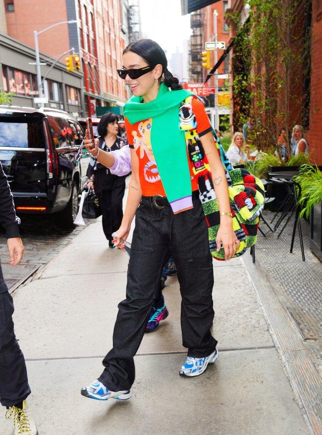 Cantora Dua Lipa andando pelas ruas de NY com blusa colorida e cachecol verde.