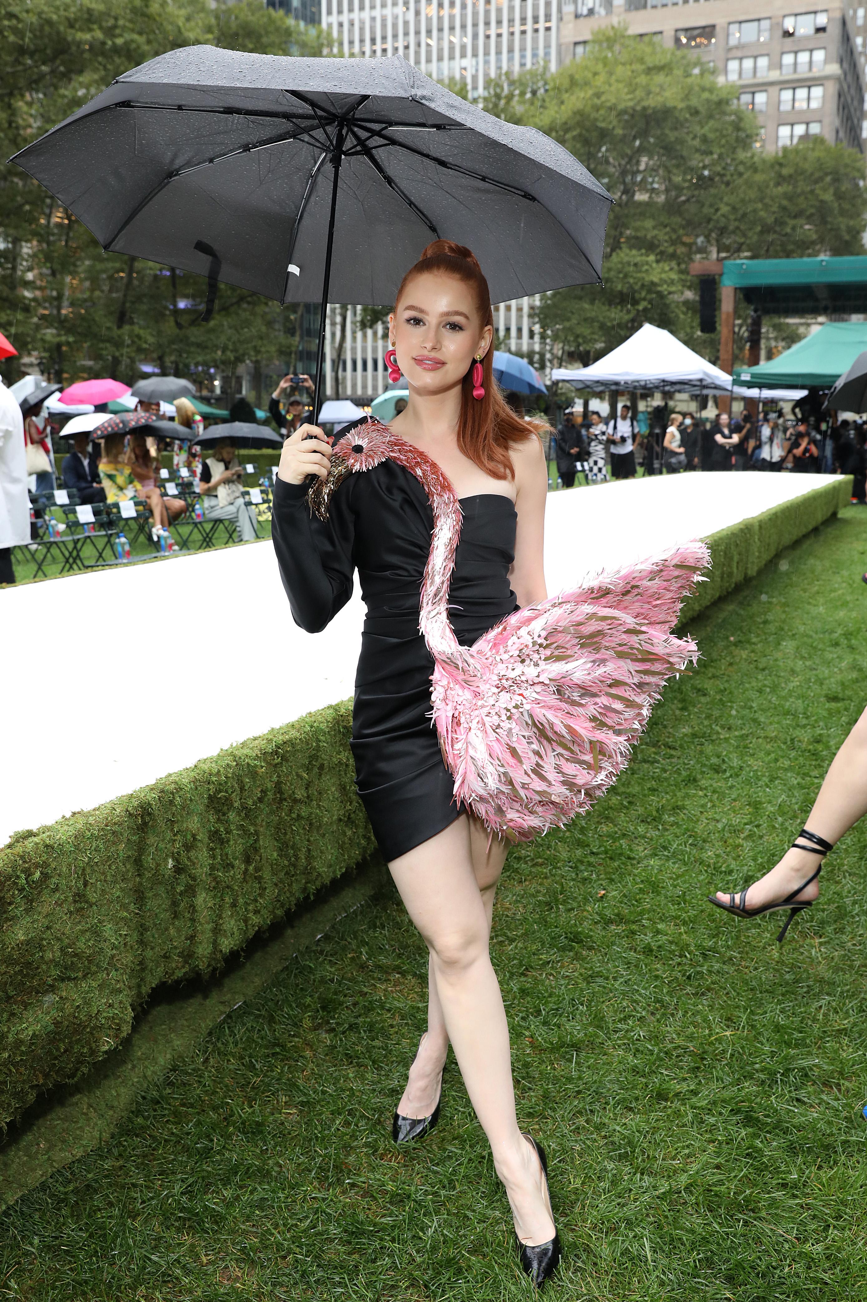 Madelaine Petsch no desfile da Moschino na semana de moda de Nova York. Ela está usando um vestido preto com um flamingo rosa e segurando um guarda-chuva na frente da passarela.