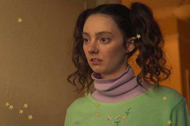 Lily, de sex Education, com expressão apreensiva e usando blusa de gola alta lilás.