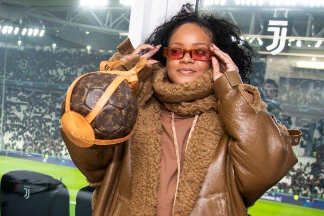 Rihanna ajustando seu óculos vermelho usando bolsa que lembra bola de basquete.