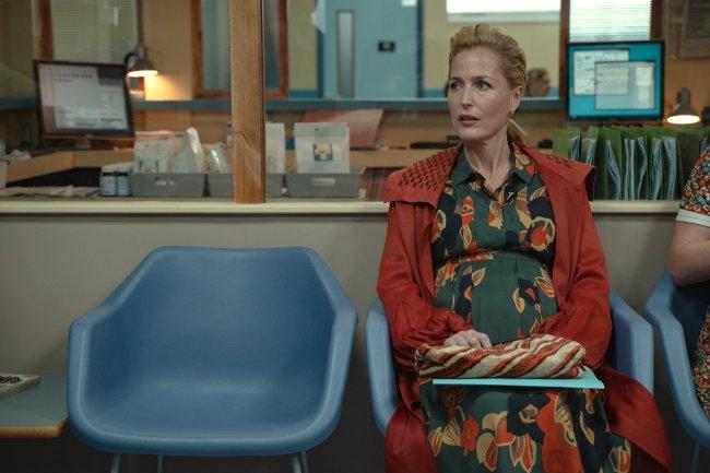 Jean Milburn, de Sex Education, sentada na sala de espera do hospital, sozinha, enquanto espera pra fazer um ultrassom