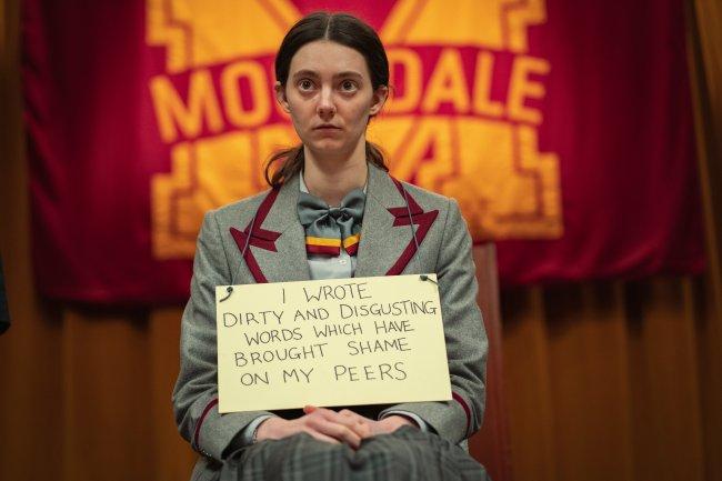 Lily, de Sex Education, está sentada no palco do teatro da escola, na frente de todos os alunos, usando no pescoço uma placa da vergonha, dizendo que ele escreve coisas nojentas