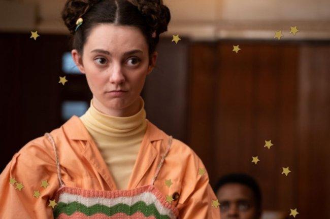 Lily, de Sex Education, com space buns, ela usa blusa bege e camisa laranja.