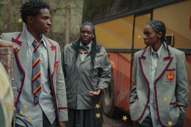 Grupo de jovens com uniforme conversando e se olhando com uma expressão apreensiva.