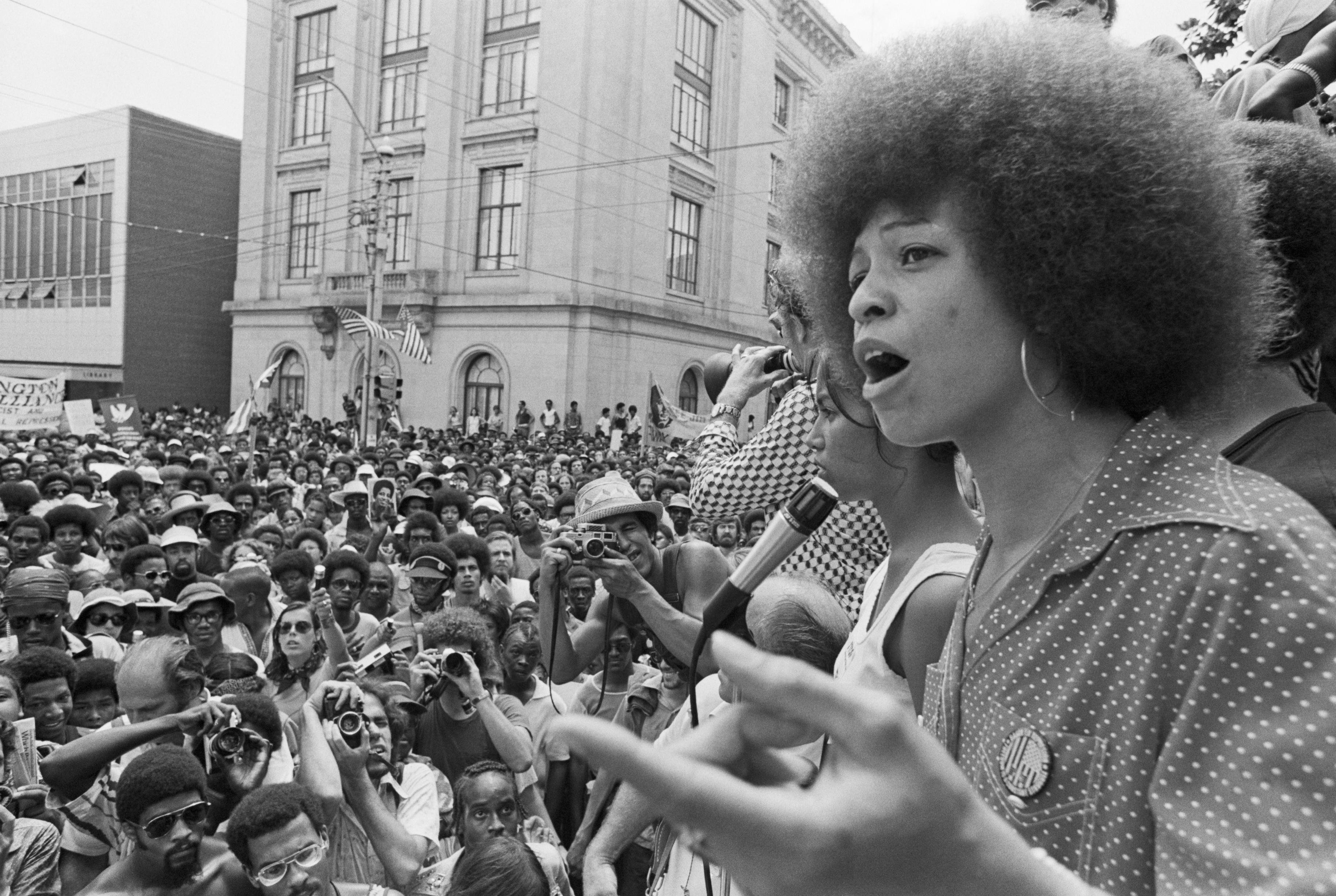 Angela Davis, à direita, discursando para um público em 1974. A foto é em preto e branco.