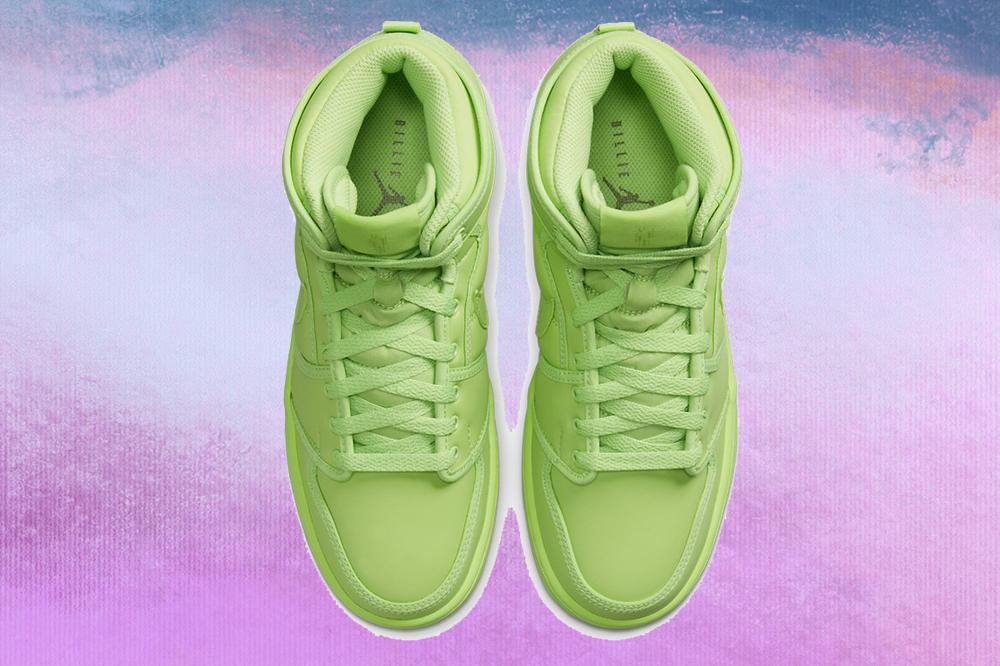 Foto do tênis verde neon no modelo Air Jordan 1 KO da coleção da Billie Eilish com a Nike em fundo lilás, roxo e azul