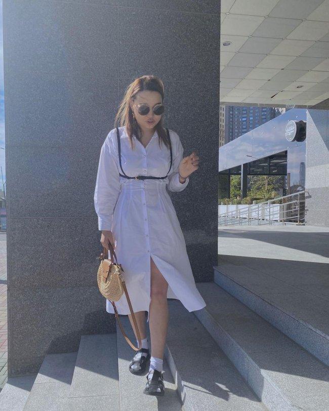 Jovem de pé posando olhando para o chão, ela usa camisa grande e sandália preta.