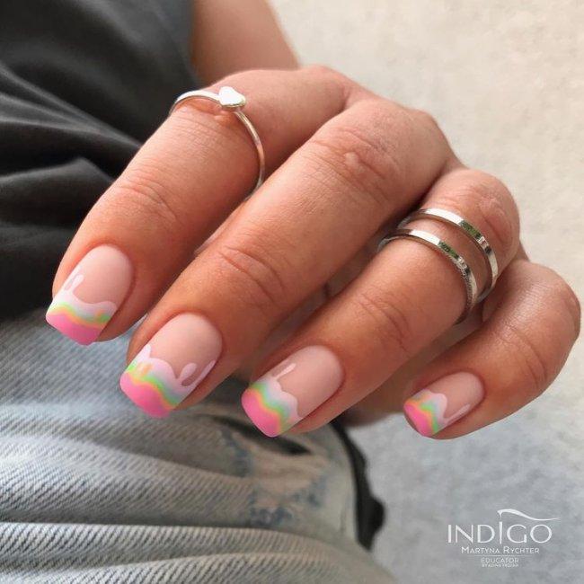 Foto de uma mão mostrando as unhas decoradas. As unhas estão pintadas com esmalte rosa claro com detalhes de ondinhas rosa e azul imitando a cobertura de um bolo.
