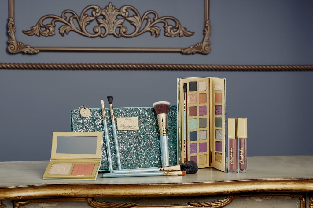 Coleção de maquiagem inspirada na Cinderela da Sigma Beauty. Na foto, há pincéis, paleta de sombras, nécessaire azul brilhante e batons líquidos.