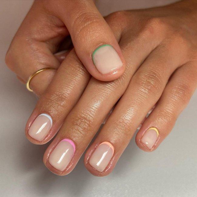 Foto com foco nas mãos, exibindo as unhas com francesinha invertida colorida.