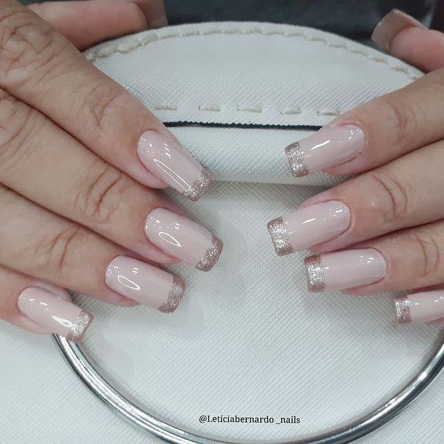 Foto com foco nas unhas feitas com francesinha de glitter.