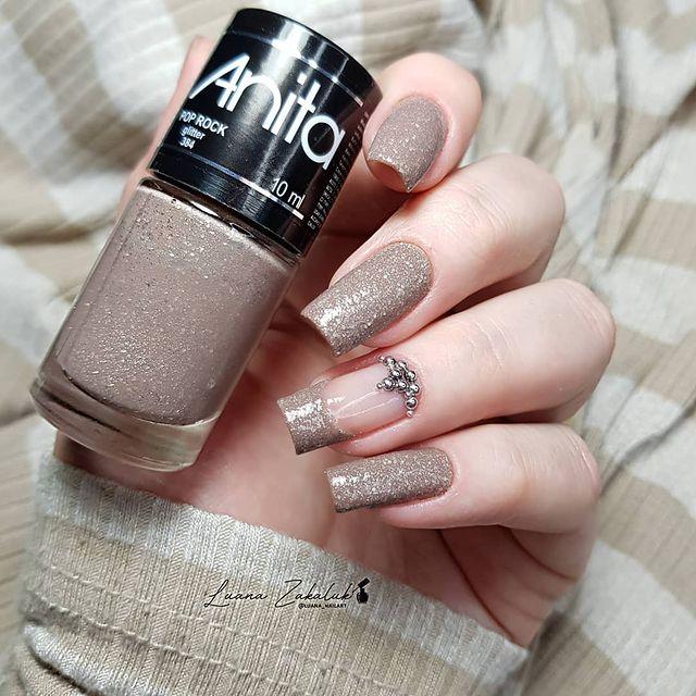 Foto de uma mão segurando um esmalte e exibindo as unhas com glitter nas pontas.