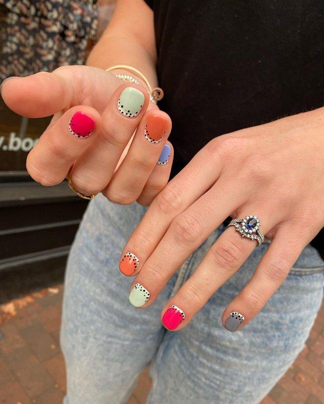 Foto com foco nas mãos, exibindo as unhas com francesinha invertida colorida com laranja, verde, rosa e cinza e detalhes de bolinhas pretas.