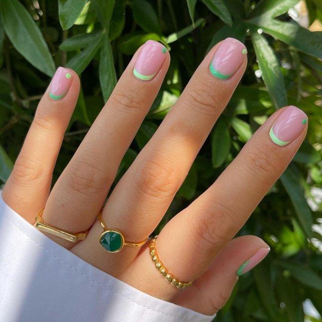 Foto com foco nas mãos, exibindo as unhas com francesinha invertida verde.