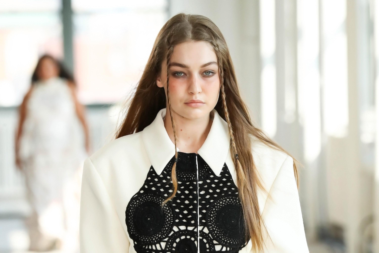 Gigi Hadid no desfile de primavera-verão 2022 da Altuzarra na semana de moda de Nova York. Ela está com expressão facial séria, trancinhas na franja, camisa branca e detalhe preto no decote.