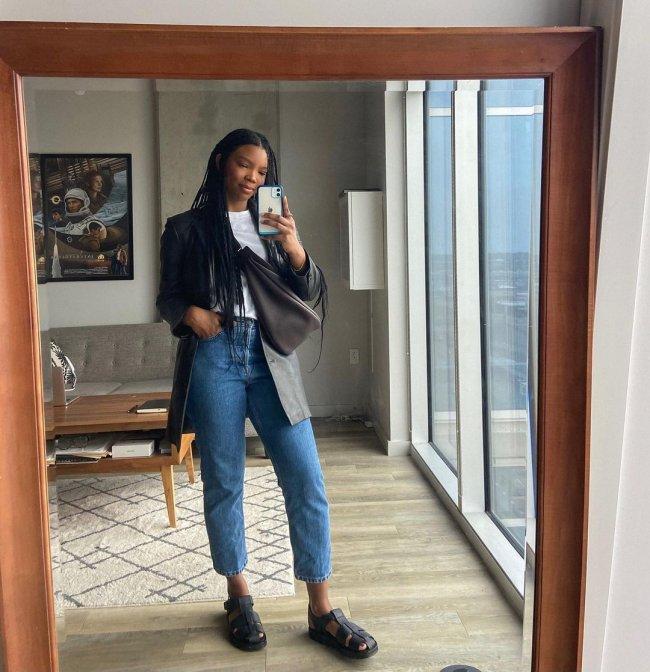 Jovem posando frente a espelho usando blusa preta e com o celular cobrindo parte de seu rosto.