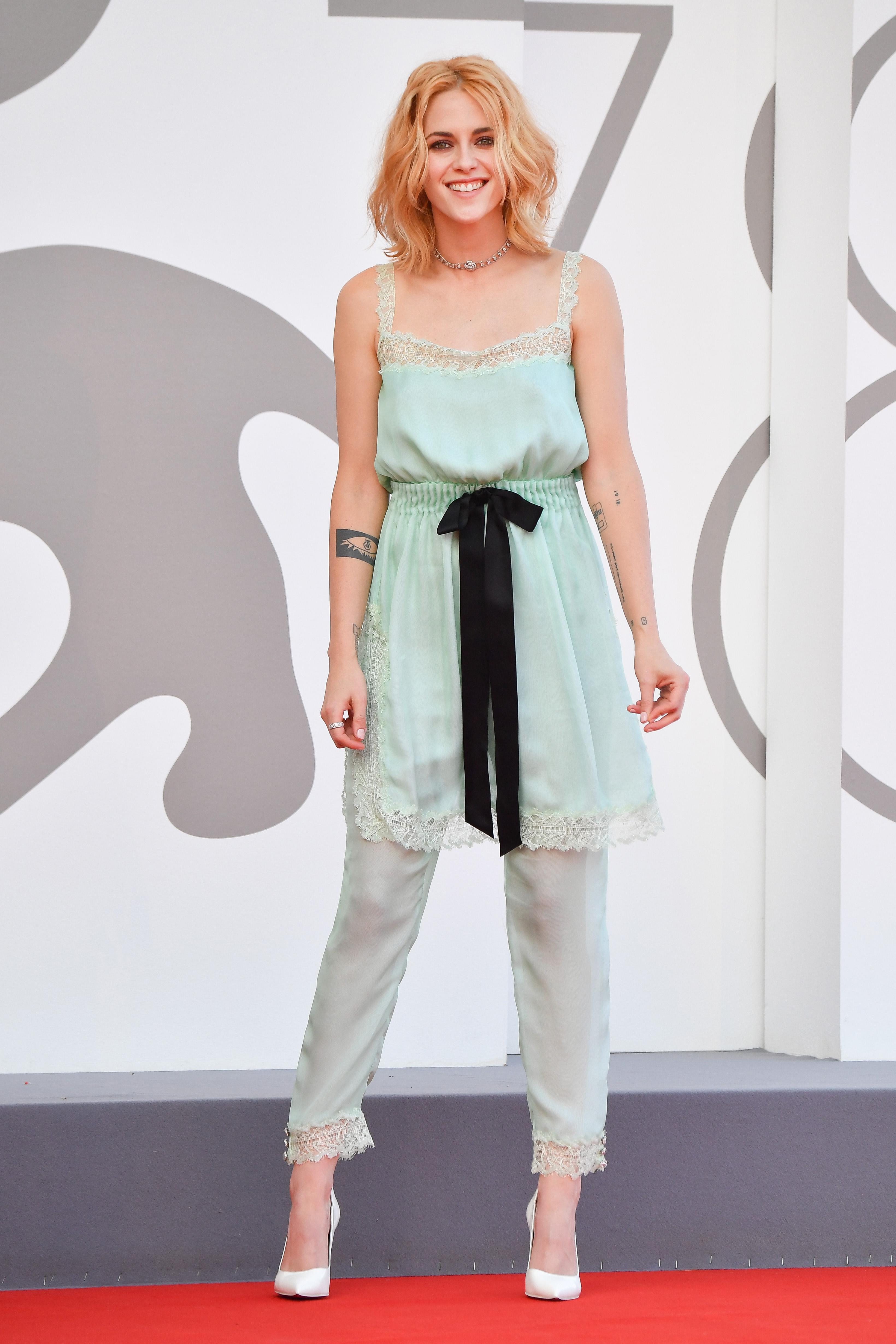 Kristen Stewart no tapete vermelho de Spencer, no Festival de Cinema de Veneza. Ela está usando um vestido por cima de uma calça em tom de verde-água com um scarpin branco. Ela está sorrindo e com o cabelo loiro solto.