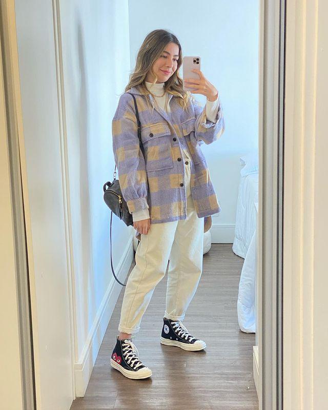 Selfie no espelho de uma mulher. Ela usa um casaco xadrez roxo e amarelo, calça branca, tênis preto de cano alto com estampa de coração e mini mochila preta. Ela olha para o celular e sorri levemente.