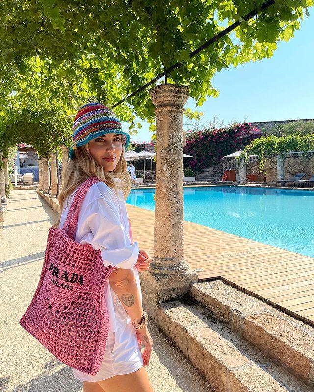 Foto de uma mulher em um espaço com árvores em frente a uma piscina. Ela usa um chapéu de crochê colorido, camisa branca e bolsa de crochê rosa da Prada. Ela está de perfil, olha para a câmera e sorri.
