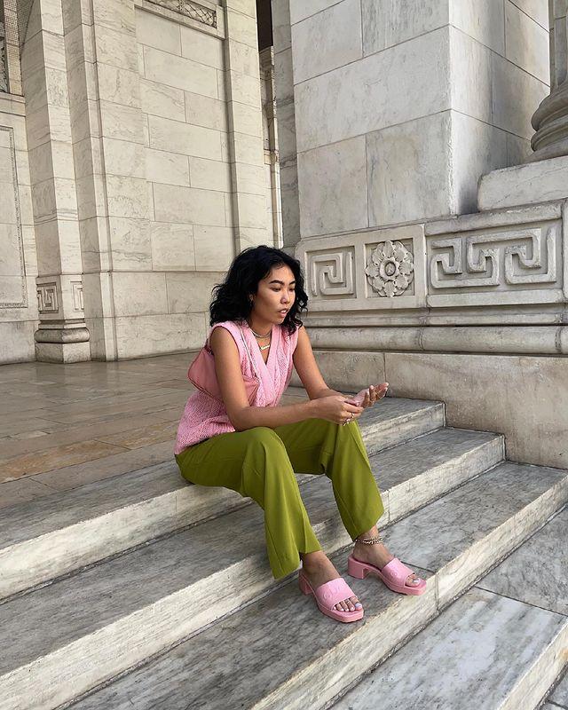 Foto de uma mulher sentada em uma escada. Ela usa um colete de vovô em um tom de rosa pastel, calça de alfaiataria verde e tamanco rosa pastel. Ela olha para frente e não sorri.