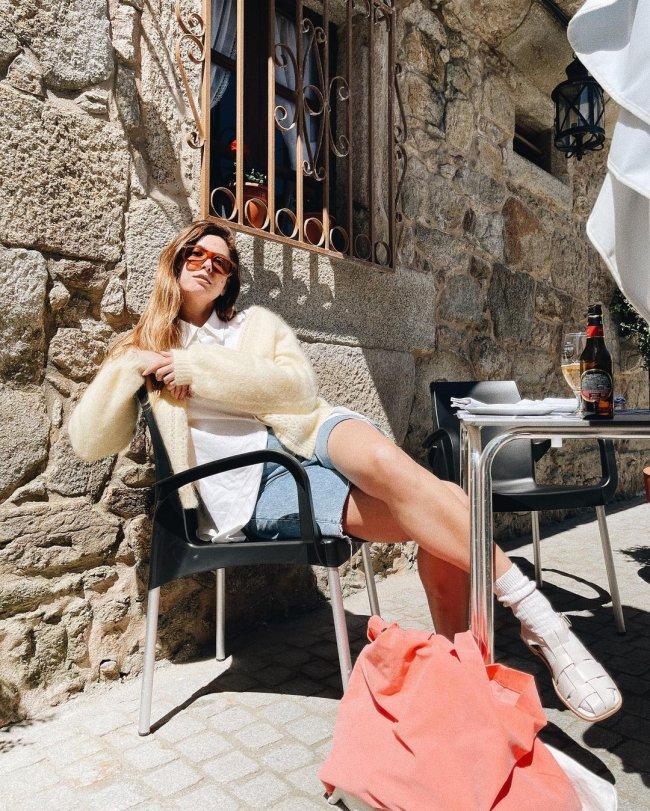 Jovem sentada em uma cadeira com expressão séria e usando óculos. Ela está com as pernas cruzadas.