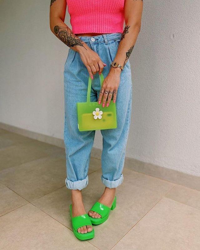 Foto do look de uma mulher. Ela usa uma blusa rosa, calça mom jeans, bolsa verde e tamanco verde. A foto não mostra o rosto dela.