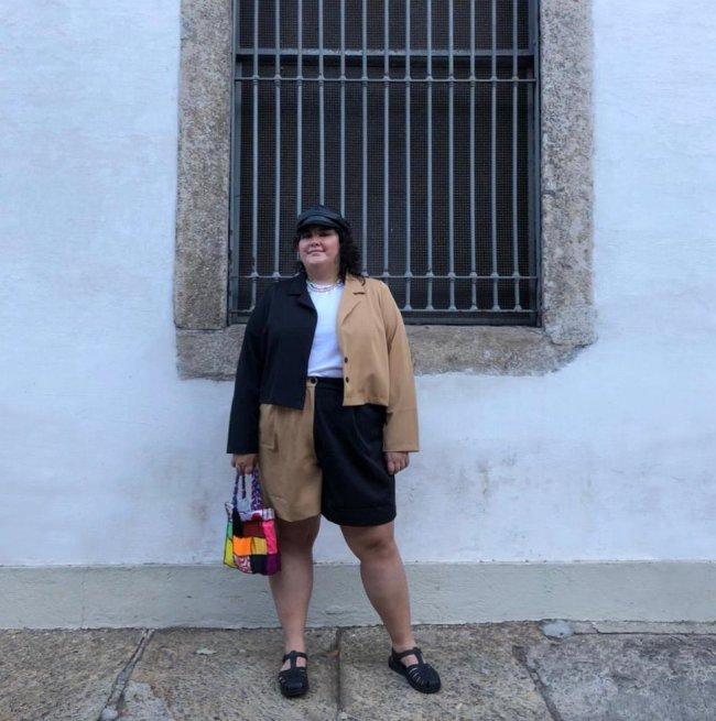 Jovem posando frente a parede branca usando conjunto de peças preta e marrom.