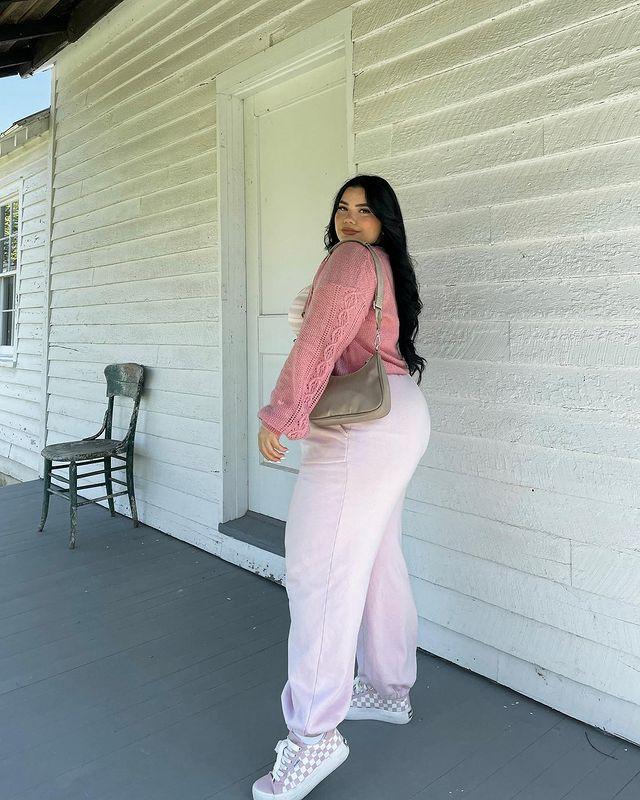 Foto de uma mulher em um corredor. Ela usa um cardigan rosa, calça moletom rosa e tênis rosa quadriculado. Ela olha para a câmera e sorri levemente.