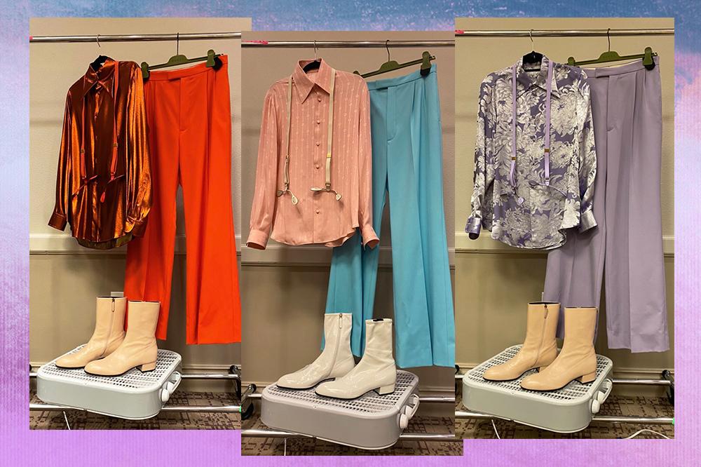 Montagem em fundo degradê lilás e azul com três looks usados por Harry Styles em sua turnê nos Estados Unidos. À esquerda, camisa laranja cintilante com calça pantalona laranja e bota em tom de creme. Ao meio, camisa rosa com calça azul e bota branca. À direita, camisa lilás cintilante, calça lilás e bota em tom de creme.