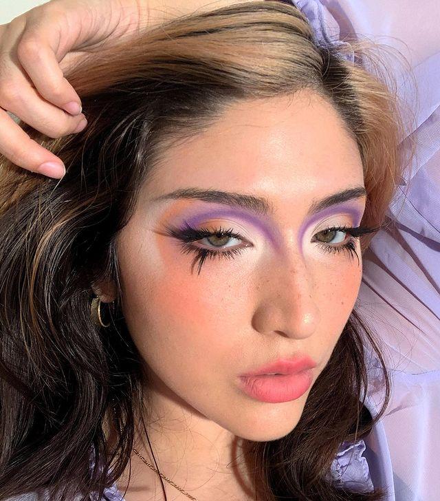 Selfie de uma mulher. Ela está com o cabelo solto, maquiagem com sombra colorida, cílio postiço nos cílios inferiores e pele básica. Ela olha para a câmera e não sorri.