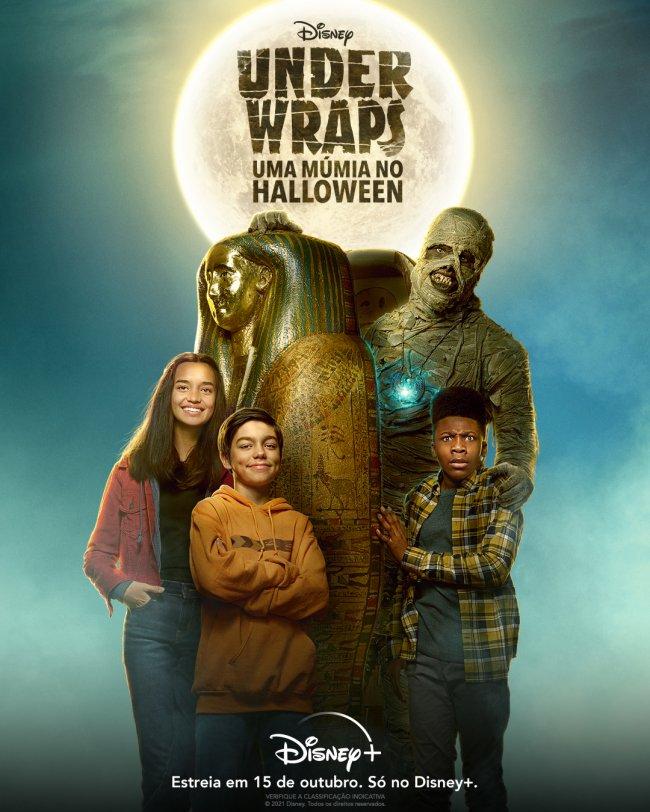 Foto de divulgação do filme Under Wraps: Uma Múmia no Halloween. Nela, aparecem três crianças posando ao lado de uma múmia. Ao fundo, temos a lua cheia e o céu escuro.