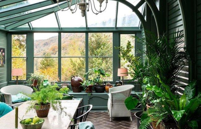 Foto de uma sala de jantar verde, cheia de janelas, bem arejada, com muitas plantinhas