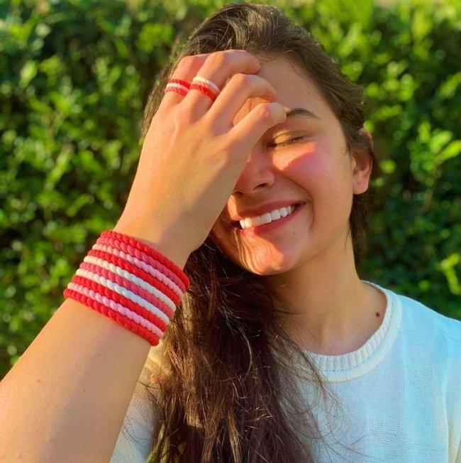 Jovem com uma das mãos no rosto. Ela usa pulseiras e anel nas cores rosa e vermelho.