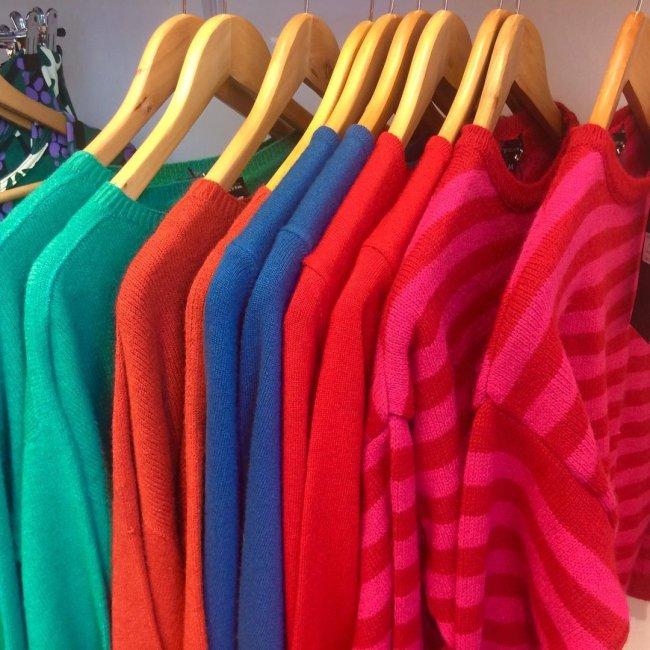 Arara com blusas coloridas penduradas, nas cores verde, azul, vermelho e rosa.