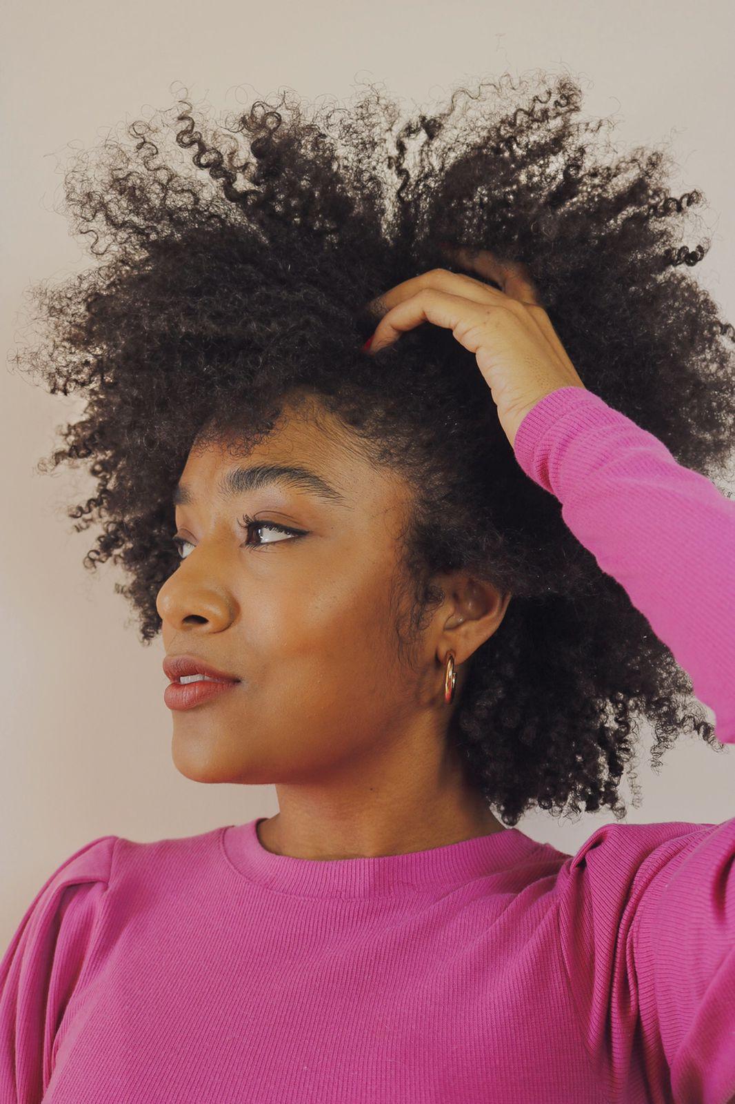 A influenciadora Sah Oliveira usando blusa rosa de manga longa, olhando para o lado com uma das mãos em seu cabelo crespo