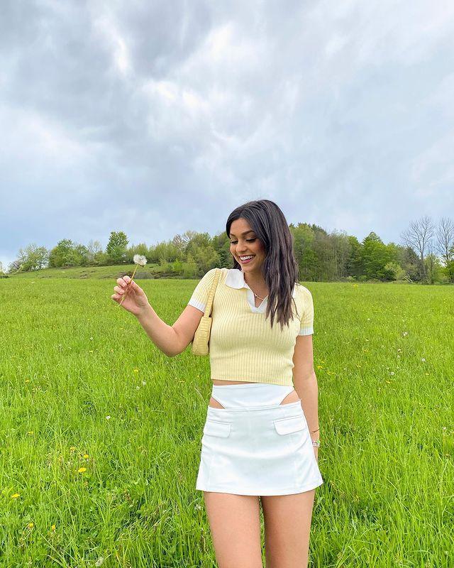 Jovem posando em gramado com expressão sorridente usando camisa polo e saia branca com recorte.