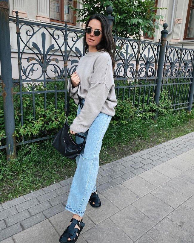 Jovem posando em frente a portão com gramado, ela segura sua bolsa e levanta a perna direita para foto.