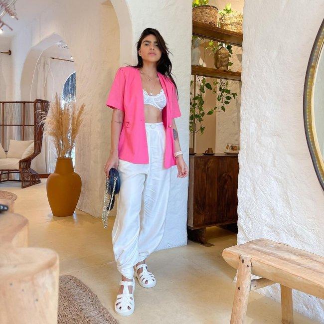 Jovem posando no meio de um cômodo com paredes brancas; ela usa top branco e camisa rosa aberta por cima; calça branca e sandália da mesma cor.