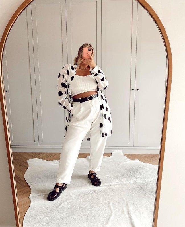 Jovem posando em frente a espelho usando look preto e branco.