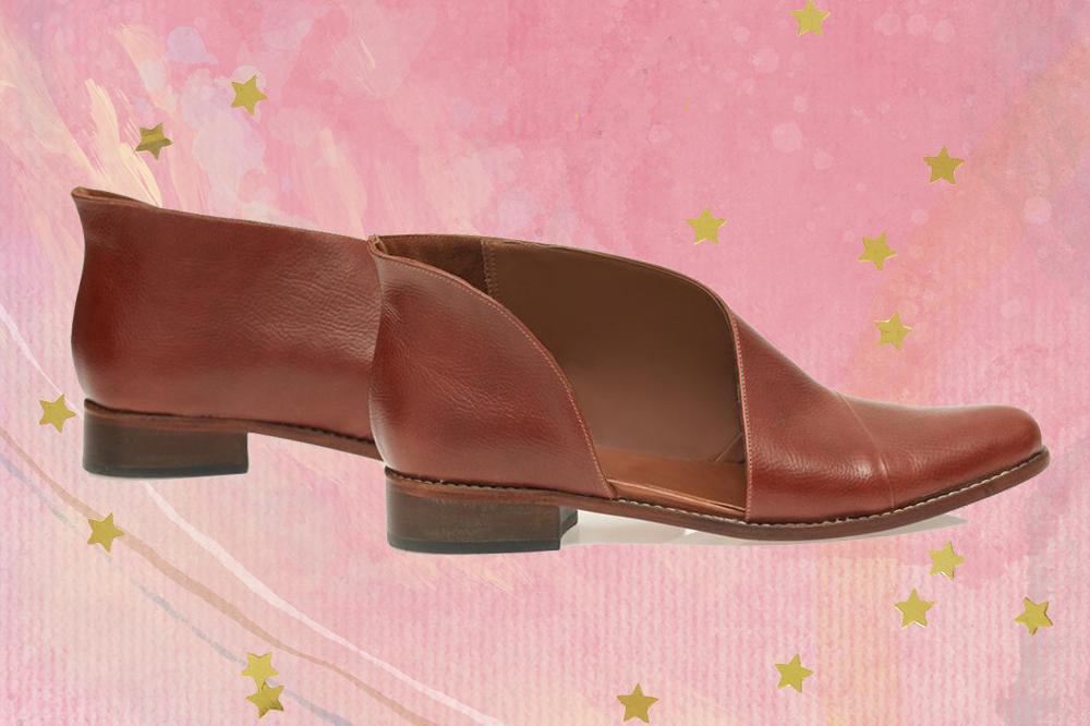 Bota de cano baixo marrom com recorte na lateral em fundo rosa com estrelinhas douradas