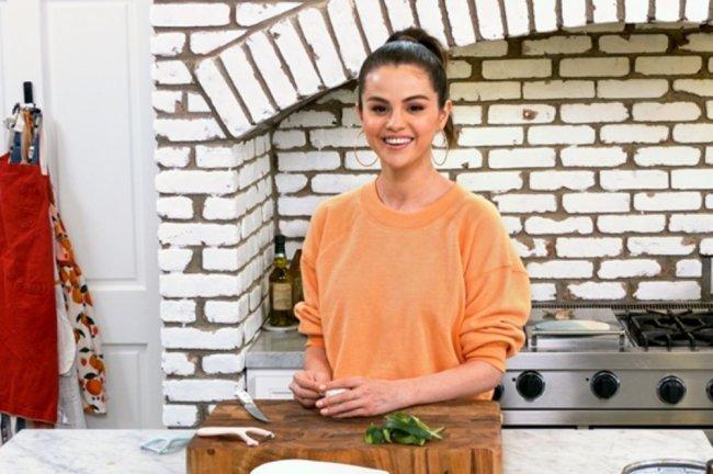 Foto de divulgação da série Selena + Chef. Nela, Selena Gomez aparece com um casaco laranja em sua cozinha, cortando um vegetal em uma tábua.