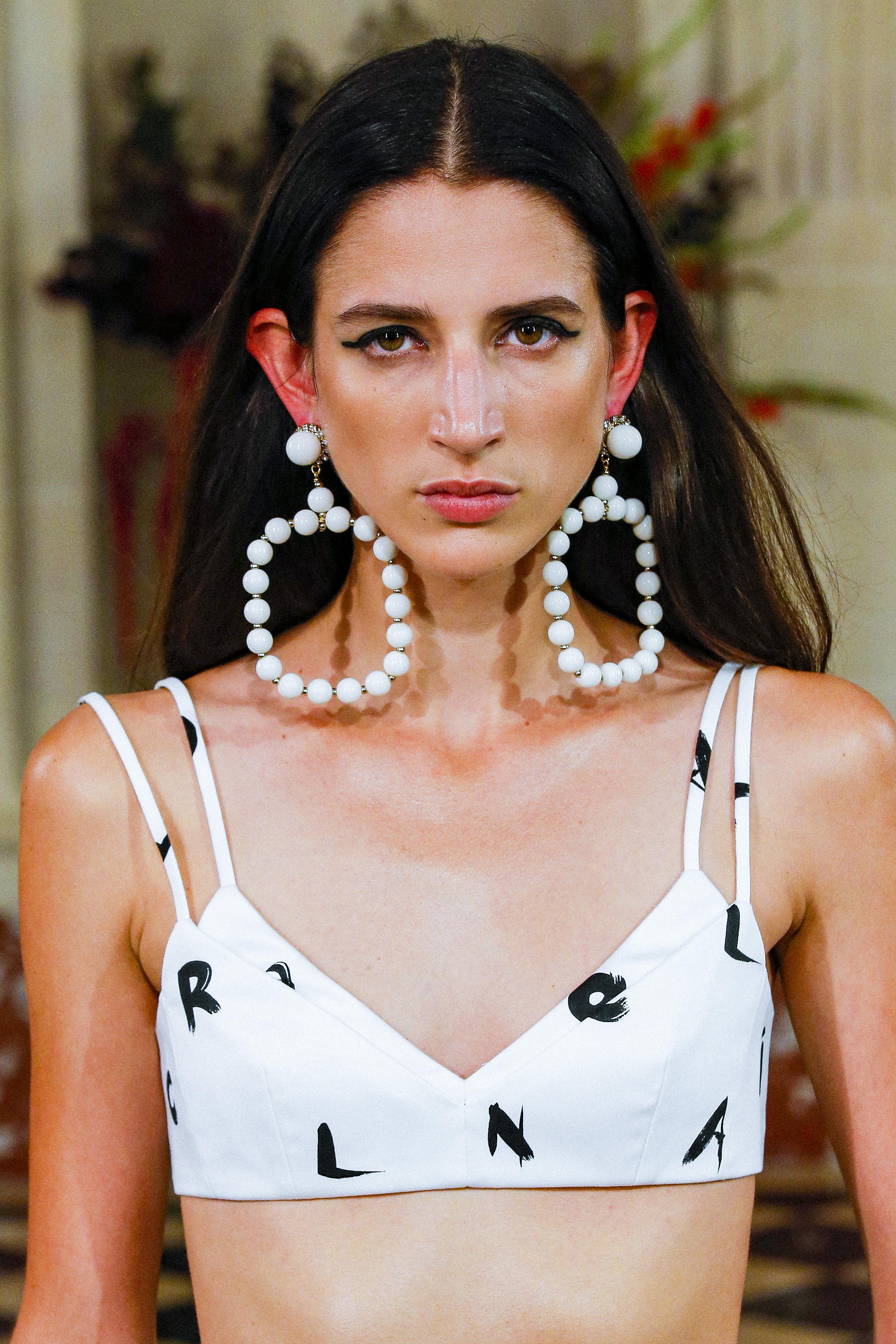 Modelo no desfile primavera-verão 2022 da Carolina Herrera na semana de moda de Nova York. Ela está com expressão facial séria, cabelo solto para trás, delineado preto, maxibrinco branco e dá para ver uma parte de sua roupa preta e branca.