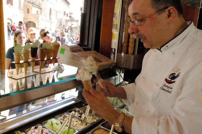 Um senhor de bigode enchendo uma casquinha com sorvete enquanto clientes animadas aguardam seus pedidos