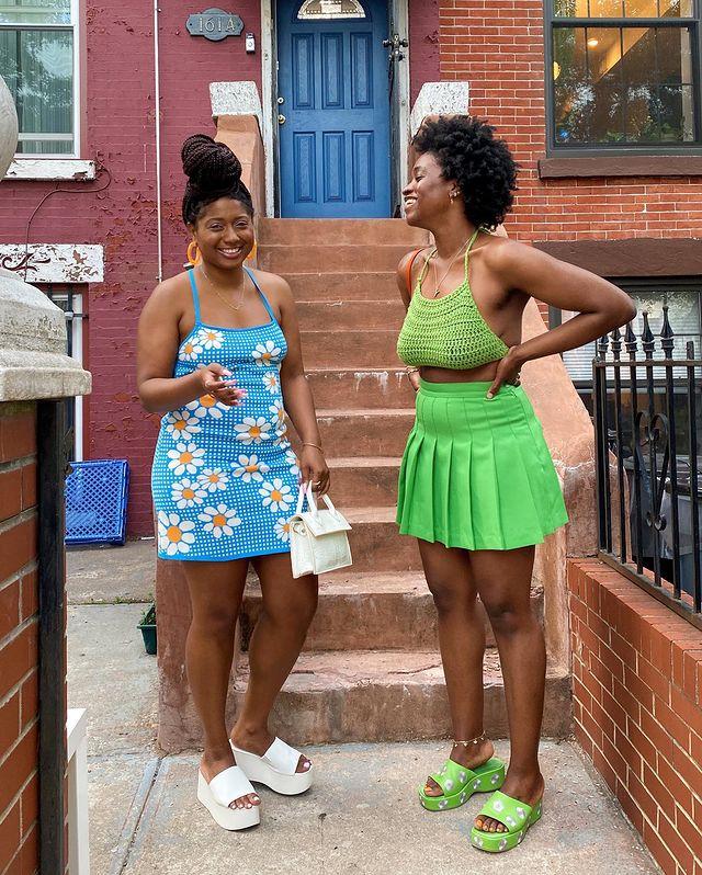 Foto de duas mulheres em uma calçada. A mulher da esquerda usa o cabelo preso em um coque, vestido azul com estampa de margaridas, bolsa branca e tamanco plataforma branco. A mulher da direita está com o cabelo curto solo, cropped de crochê verde, saia verde e tamanco verde. Ambas estão sorrindo para a foto.
