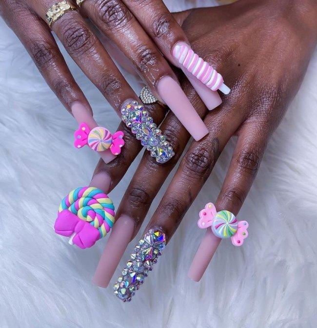 Foto de unhas decoradas. Todos as unhas estão com esmalte rosa claro e detalhes 3D de docinhos coloridos, o dedo anelar está decorados com cristais.